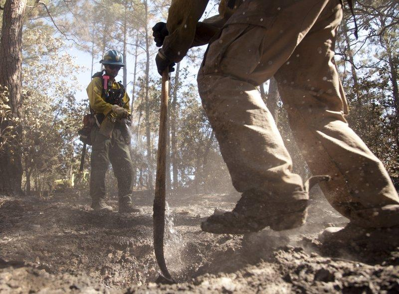 An unidentified fire crew tamps down the very last of the Bastrop wildfires, in September 2011. Central Texas is in a heightened time for wildfire risk.
