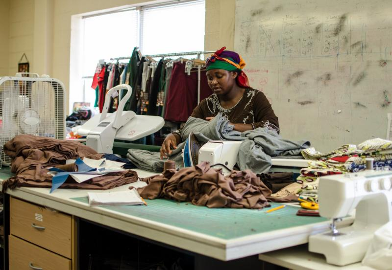 An unnamed employee of Open Arms from Burundi sorts through donated fabric. Open Arms pays refugee women a living wage to make clothes.