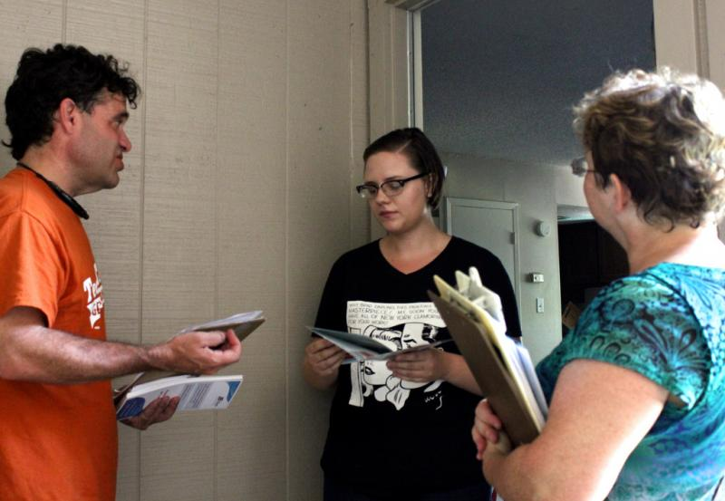 Enroll America's Kenneth Flippin, left, and Jane Denson, right, knocked on the door of Shelby Childress on Sept. 7, 2013 in Austin.