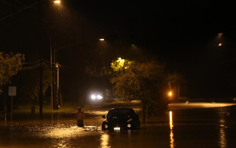 An unidentified man walks past an abandoned car along Pleasant Valley Road. Heavy rains overnight caused serious flooding all over the Central Texas area.