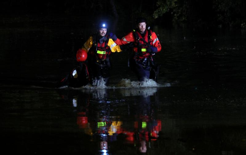Two Rescue workers emerge from the flood waters after checking for possible victims in a partially submerged car in the Onion Creek area. Heavy rains overnight caused serious flooding all over Central Texas.