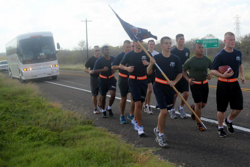 The University of Texas Naval ROTC program's annual run to Dallas is canceled due to the government shutdown. In this file photo from 2012, a group of midshipmen carry the game ball for the Red River Shootout.