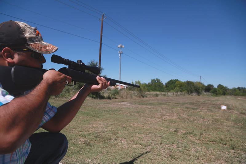 A student points a pellet gun at a paper target, required as part of the curriculum taught in the Spanish-language Hunter Education course of Texas Parks and Wildlife.