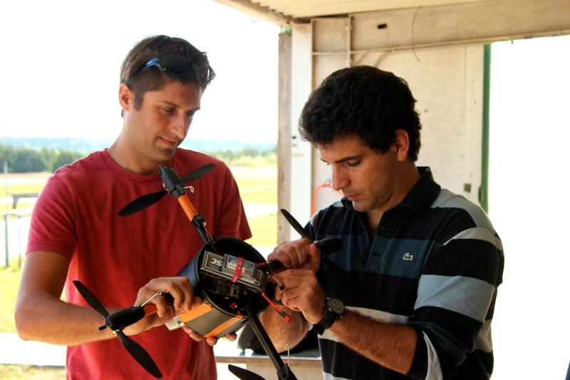 Mark Maughmer (left) and Miki Szmuk (right) strap a camera on to the unmanned aerial vehicle engineered at the Cockrell School of Engineering.