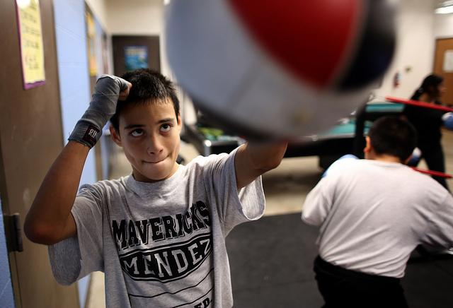 After warm-ups, students practice on separate punching bags before sparring or practicing with mitts in the ring.