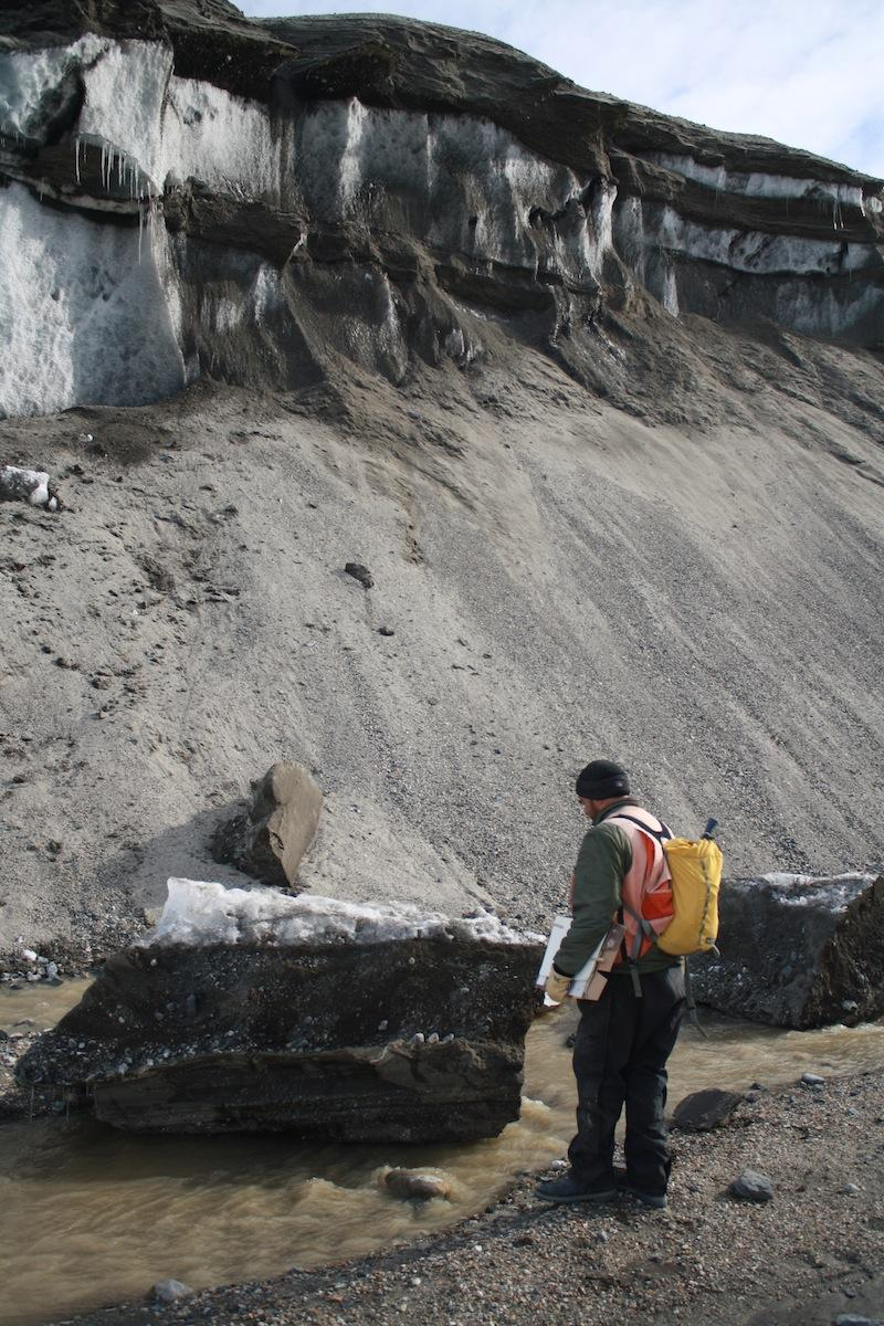 An Antarctic researcher inspects a block of frozen ground (permafrost) that has tumbled down into the Garwood River, where it will melt rapidly. Because of the shutdown, researchers haven't been able to complete the third and final year of their study.