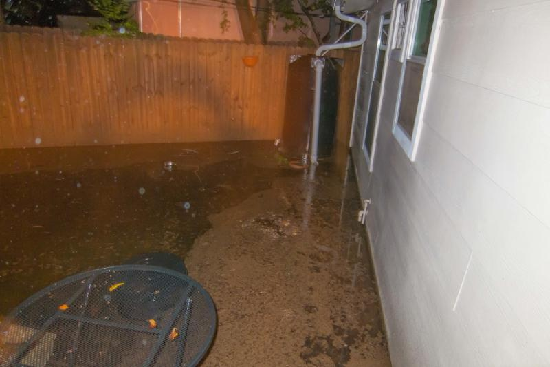 """In South Austin's Southwood neighborhood, off of Clawson Road, a homeowner had to rip out the fence behind their rainwater collection system. """"You can see [it] has about four inches of rain collecting outside of it! … We never get flooded."""""""