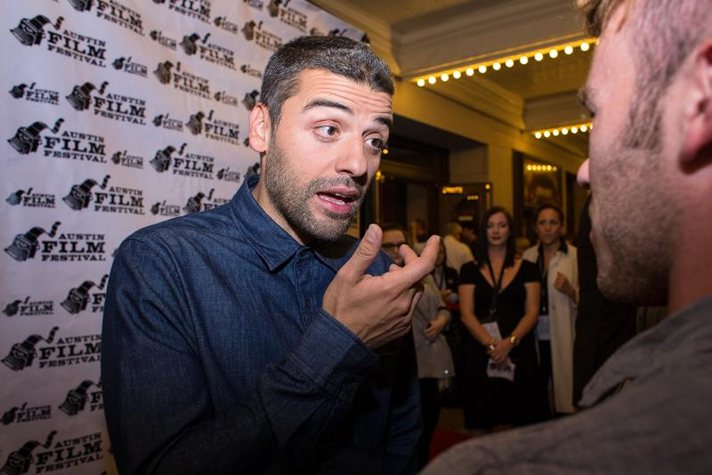 """Actor Oscar Isaac walks the red carpet prior to a screening of his upcoming movie """"Inside Llewyn Davis"""" outside the Paramount Theatre."""