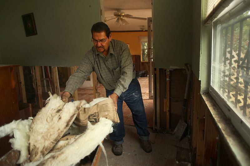 Ricardo Fabian removes damp insulation from the walls of his house in Dove Springs. Volunteers are needed to help clean up after the recent flooding in southeast Austin, but experts urge people to head down prepared.