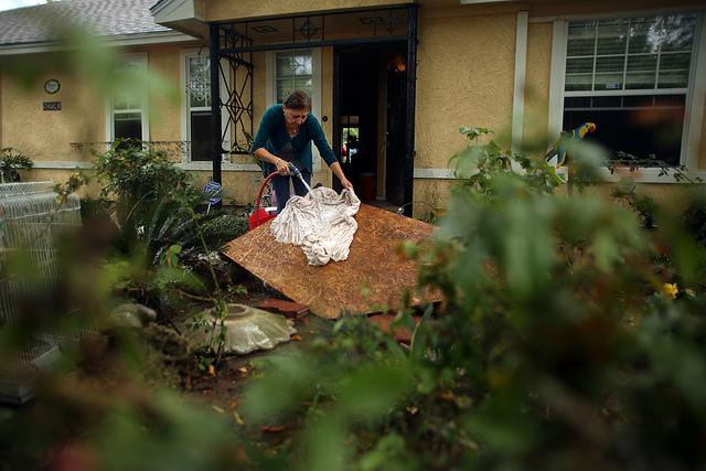 In this Nov. 4 photo, Maria Isabel Fabian tries to salvage an heirloom tablecloth from her flood-damaged home in Dove Springs. Damage from the Halloween floods is estimated at over $14 million.