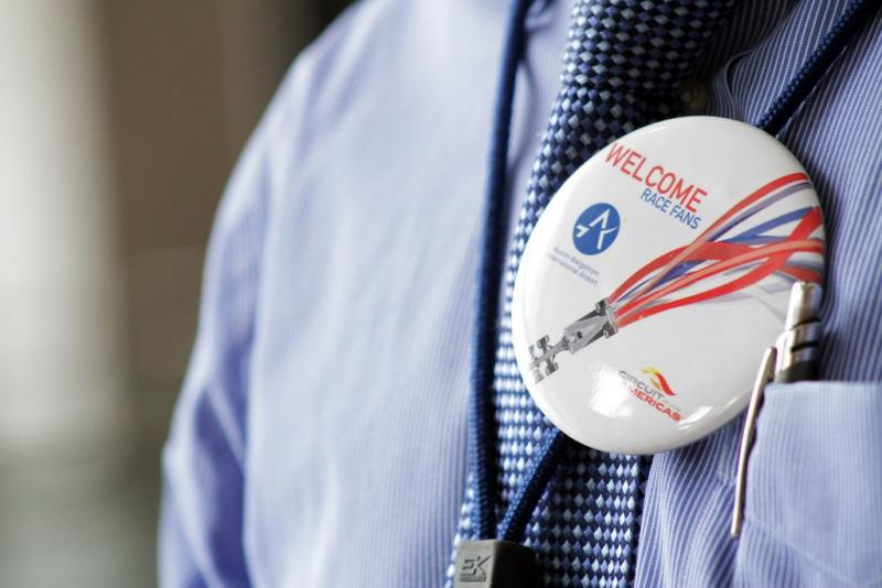 An airport employee's pin greets Formula 1 crowds in this 2012 photo.