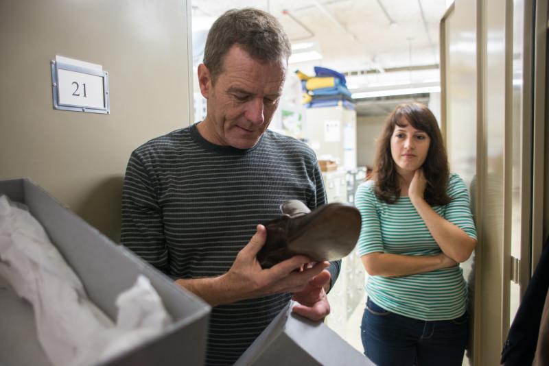Cranston examines LBJ's shoes. LBJ Library staffer Sara Nezamabadi looks on.