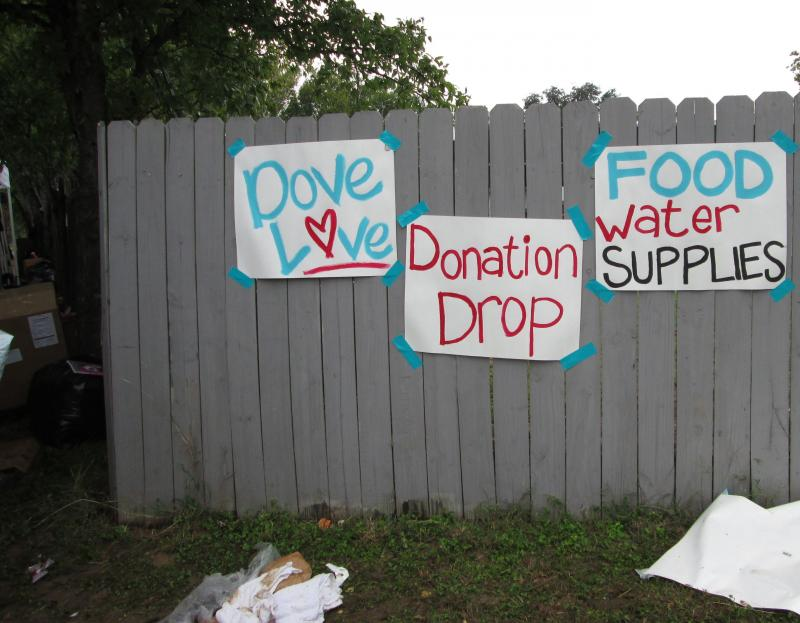 "Signs near a donation drop-off point in the Dove Springs area read ""Dove Love."""