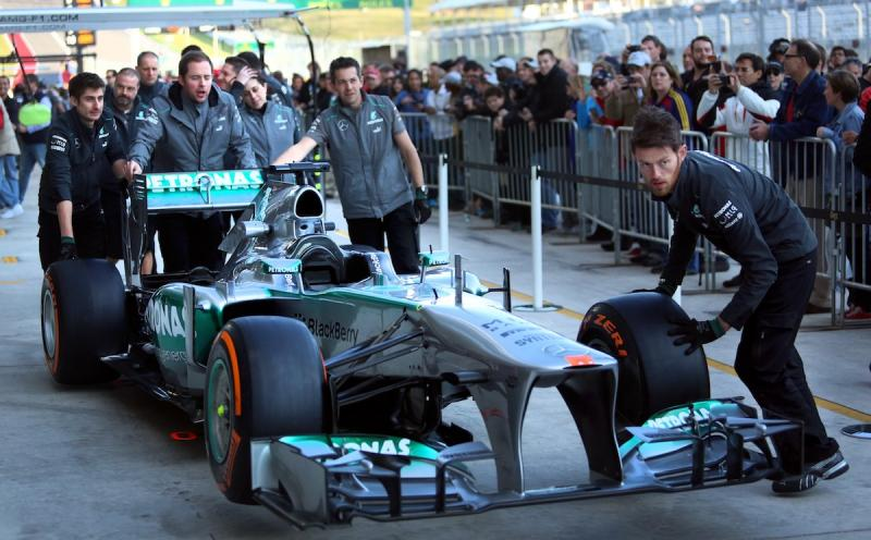 The Petronas team rolls a car down pit lane as hundreds of spectators look on.