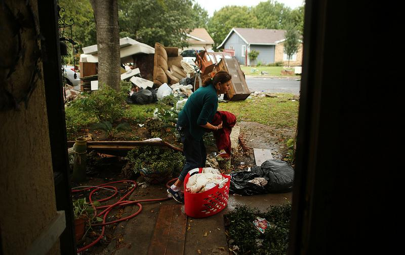 Maria Isabel Fabian sorts through clothes salvaged from her Dove Springs home which flooded when record rains hit the Austin area on Thursday, Oct. 31, 2013.
