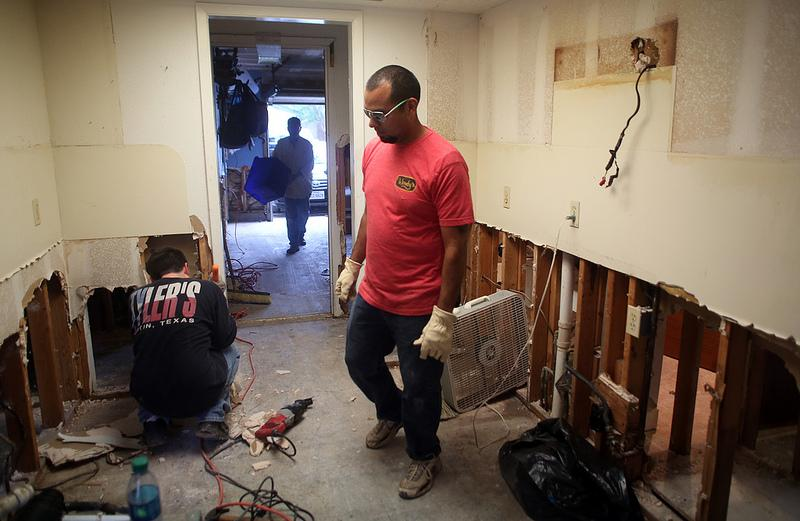 Mike Espinoza gets help pulling damp sheetrock from the kitchen of his home. He and his wife waited out the sudden flood in the second floor of their Onion Creek home.