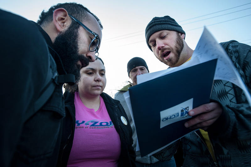 ECHO team leader Ben King shows Ruy Manrique, Mia Ibarra and Jason Wible their section on a map prior to departure.