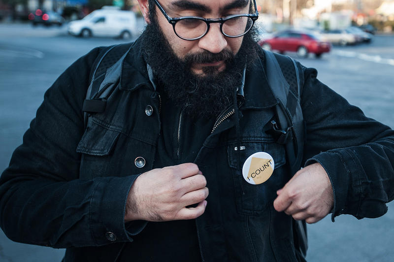 Volunteer Ruy Manrique pins a button to his jacket that serves to identify him during the count.