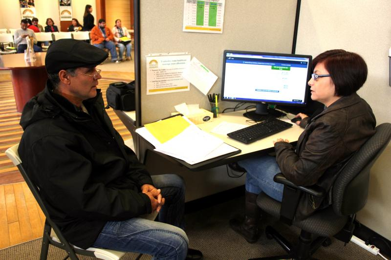 Ovidio Jesus Garcia, left, gets help from Gigi Veliz at Foundation Communities' Insure Central Texas location at Highland Mall on Jan. 14, 2014.