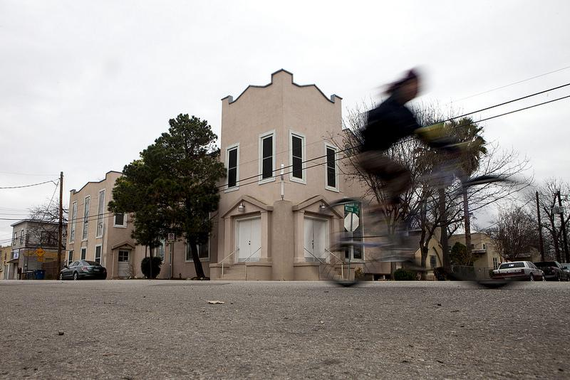 A cyclist passes El Buen Pastor Early Childhood Development Center on the Tejano Healthy Walking Trail in East Austin.
