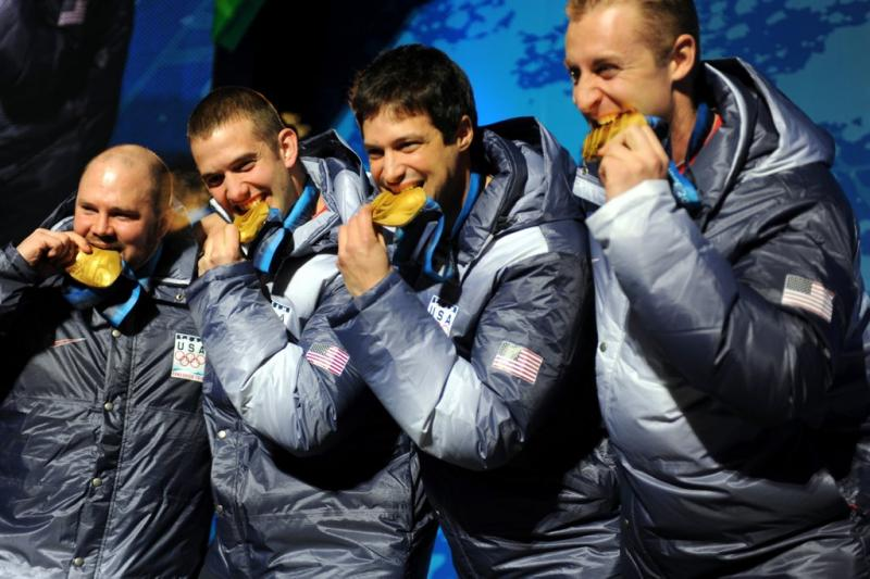 U.S. bobsledder Justin Olsen (second from left) and teammates Steven Holcomb, Steve Mesler and Curt Tomasevicz bite their gold medals after winning the Olympic four-man bobsled honors in the 2010 Winter Olympics.