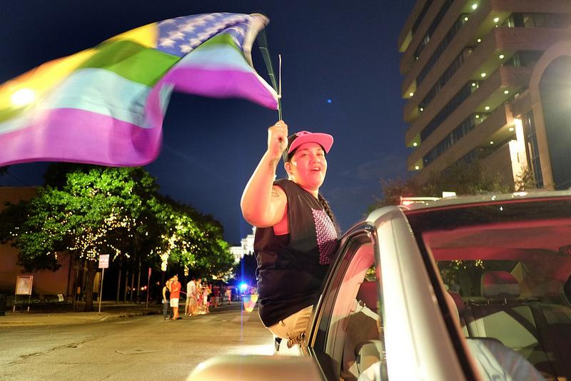 Cori Samilpa of Austin waves an LGBT flag as the 2013 Austin Pride Parade makes its way down Congress Avenue.