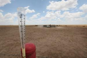 An empty rain gauge is strapped to a fence post on the edge of a pasture this summer near Canadian, Texas.