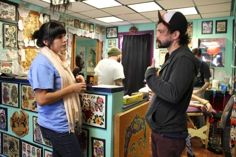 A field organizer with Insure Central Texas speaks to staff at an Austin tattoo parlor in the last few days before the March 31 deadline to sign up for health insurance.