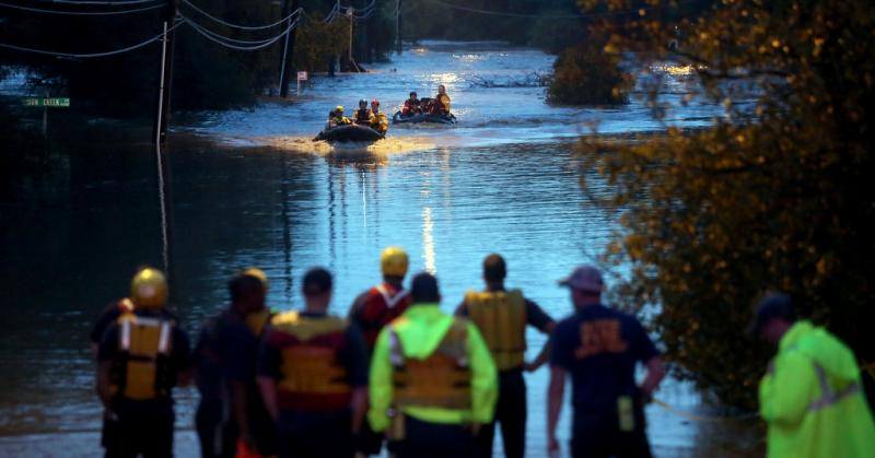 Rescue teams in Southeast Austin assist people stranded in rising flood waters in the early hours of Oct. 31, 2013. A city report faults officials for late activation of an emergency response center, among other shortcomings.