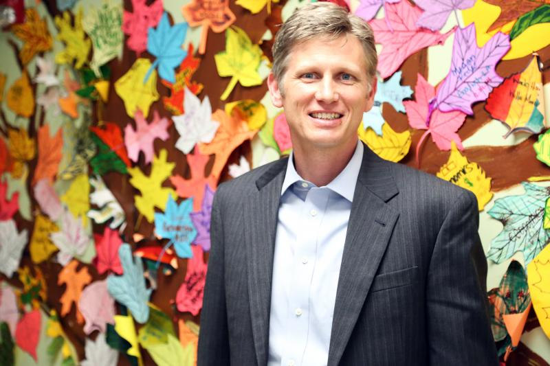 Parc Smith is American Youthworks' CEO. He stands by a tree that highlights the achievements of his students. Students follow a self-paced program until they finally graduate high school.