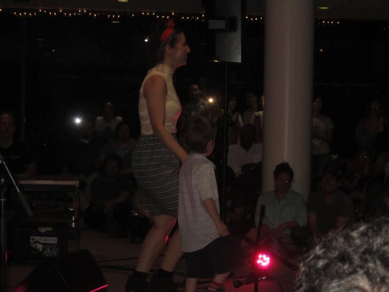 Cafetera Leah Gallegos dances with a young audience member.