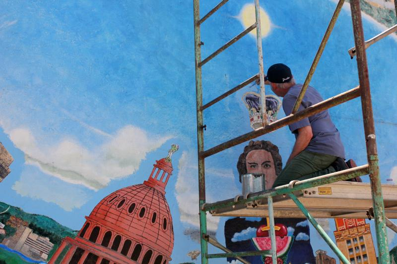 Original artist Rick Turner touches up the sky on the mural on the south wall of the University Co-op.