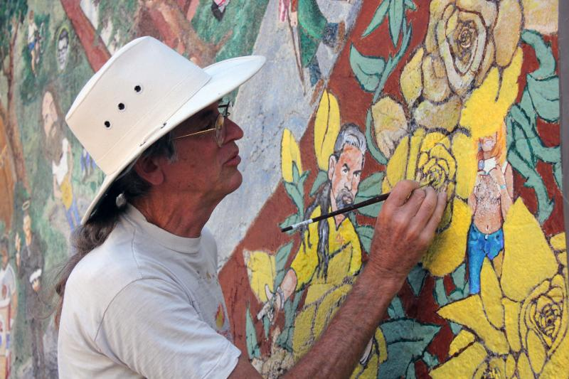Artist Tom Bauman restores a Texas yellow rose on the Austintatious Mural.