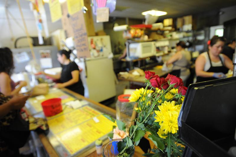 Workers prepare orders in the afternoon of the final day at Tamale House #3 on Airport Blvd. Tamale House will close in the wake of owner Robert Vasquez's death.