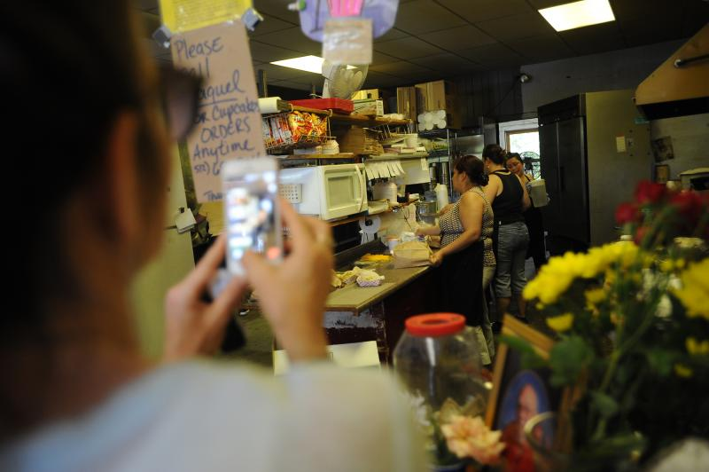 A woman records video on her phone as orders are prepared on the final day at Tamale House #3 on Airport Blvd. Tamale House will close in the wake of owner Robert Vasquez's death.