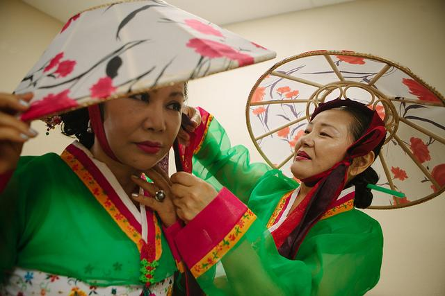 "Connie Kim adjusts Kyong Ah's hair before they take the stage to perform ""Uh Woo Dong."" a traditional Korean dance. The Korean United Pentecostal Church hosts a Parents Day celebration for parents and senior citizens of the community."