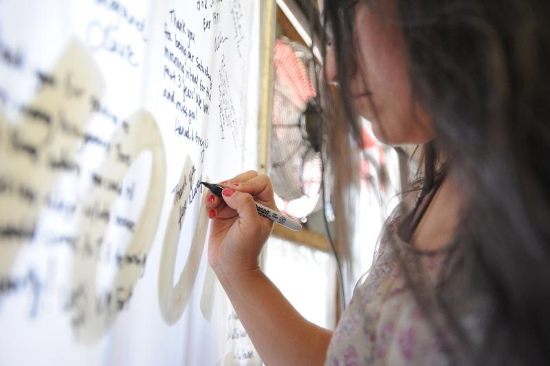 Crystle Castro writes a personal message during the final day at Tamale House #3 on Airport Blvd. Tamale House will close in the wake of owner Robert Vasquez's death.