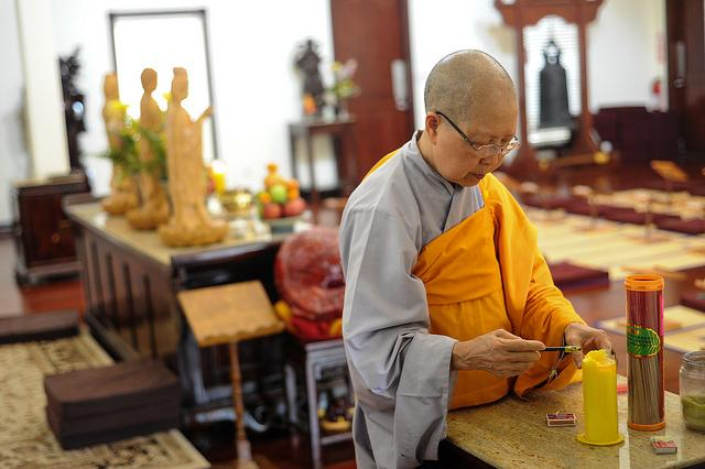A high nun prepares the altar for service at the Chua Linh-Son Buddhist Temple on Duval Road. The temple serves a Vietnamese population in North Austin.