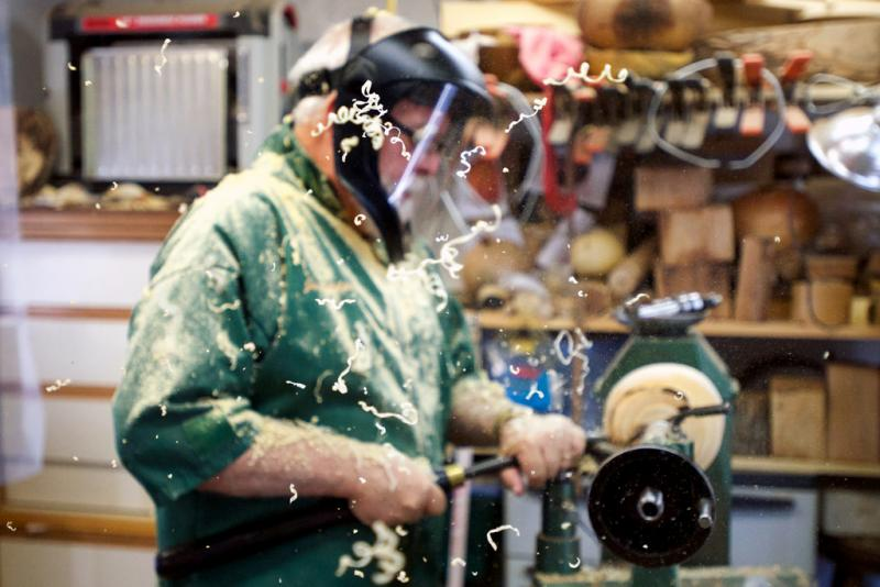 Shavings fly as master woodturner Jim Philpott carves a bowl in the workshop behind his Kyle home.