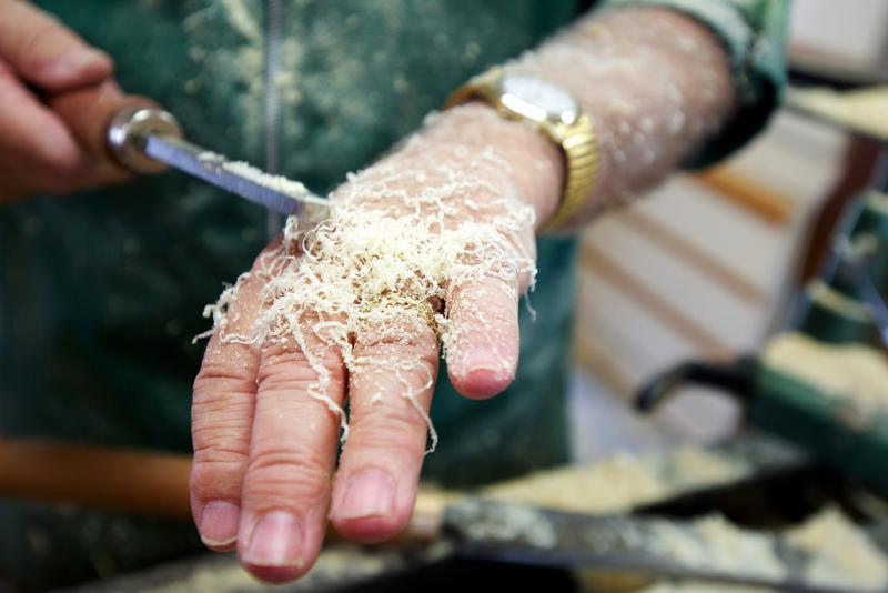 Woodturner Jim Philpott says he can tell how close a project is to completion by the size of the shavings that stick to the back of his hands. Here he points out the thinning ribbons and smaller pieces of sawdust that indicate he's getting closer.