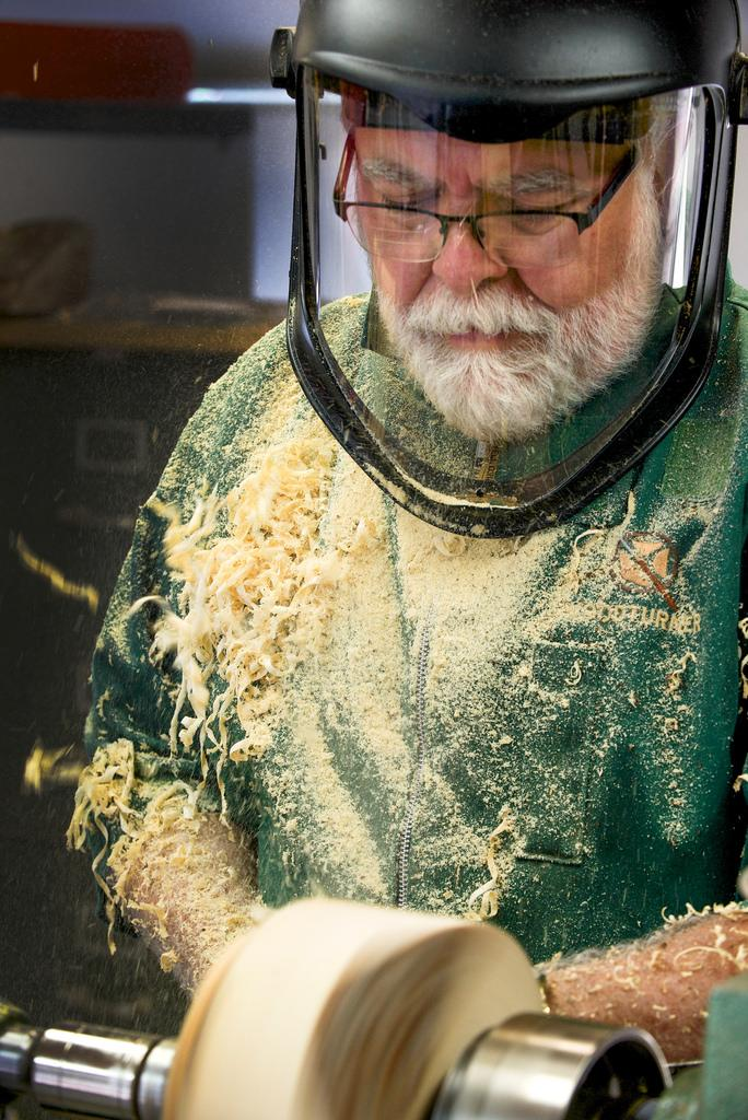 Master woodturner Jim Philpott is the model of concentration as shavings fly from a block of wood that is fast on its way to becoming a small bowl. Philpott has to stop every few minutes to brush the innumerable curly shavings and bits of dust from his cl
