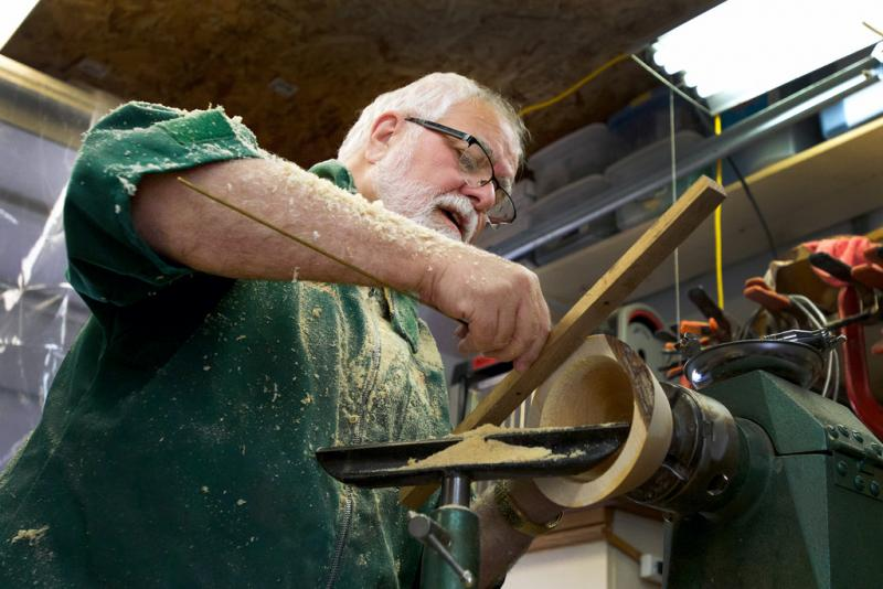 Master woodturner Jim Philpott uses a handmade gauge to check the uniformity of a bowl's edges and depth. The workshop garage behind his Kyle house is filled to the ceiling with tools and equipment.