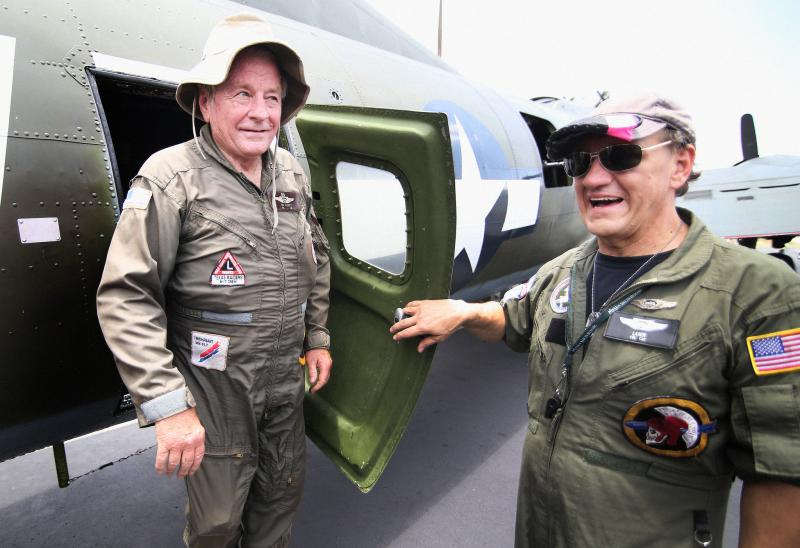 71 year-old Commemorative Air Force (CAF) Col. Pat Elliott(left) talks to passengers before a short flight over Austin.