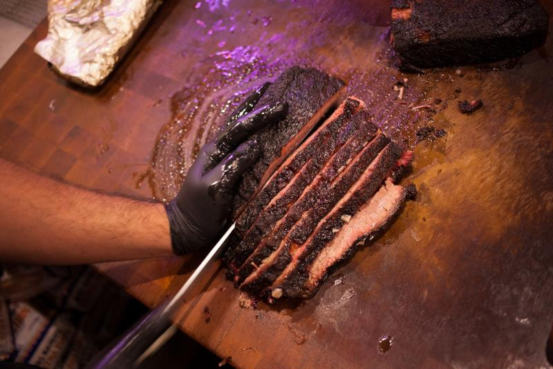 Smoked brisket is sliced at Franklin BBQ, which recently expanded operations to include an enclosed area to smoke the meat.