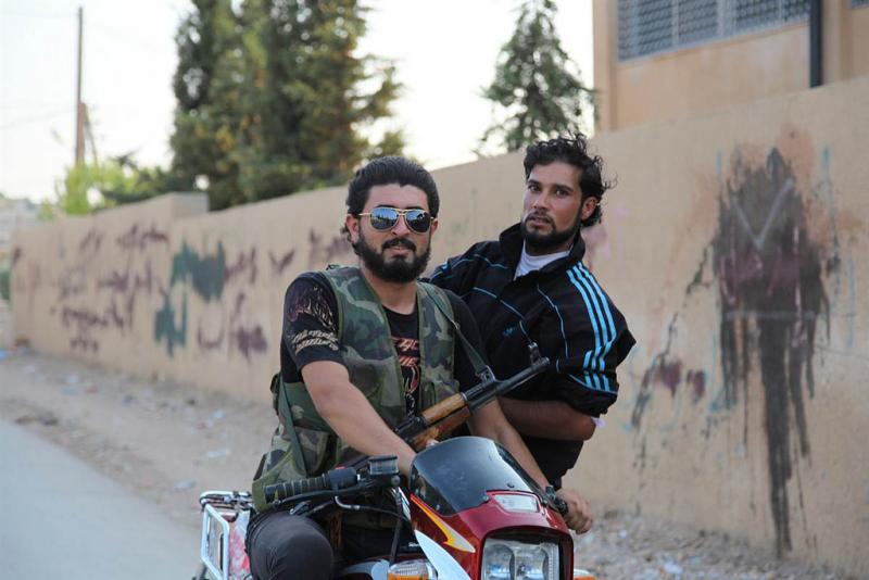 Rebels ride a motorcycle in northern Syria