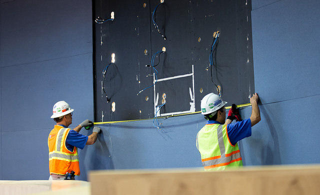 Workers measure the area formerly occupied by the chambers' television monitor.