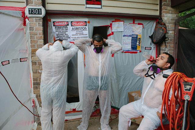 Eddie Bermude, center, and Julio Centeno, right, work for AAR Inc., a company hired to remove asbestos from most of the houses set to be demolished. The crew leader said many of the workers live in the Dove Springs neighborhood.