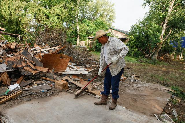 Jose Cardona, a member of a demoliton crew, sweeps up debris from a demolished home on Onion Crossing Drive.