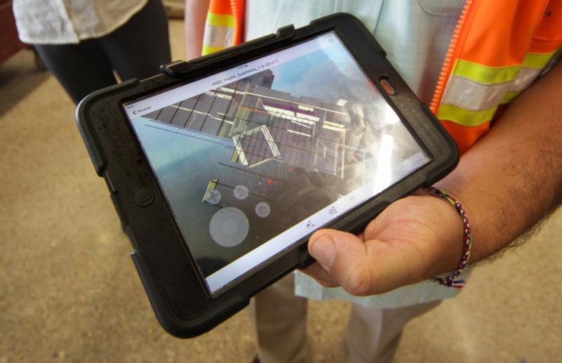 A construction foreman views schematics of a wall on his iPad.