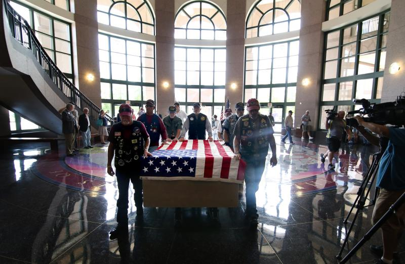 Patriot Guard Riders walk with the first crate of many which are being delivered to the Bullock Texas State History Museum.
